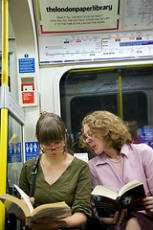 Två kvinnor har sin läsecirkel på ett pendeltåg