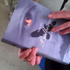 """Ett par händer som håller romanen """"Vägen till Bålberget""""."""