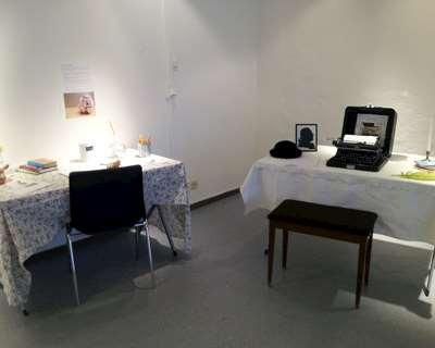 Två skrivbord ed stolar och en gammal skrivmaskin.