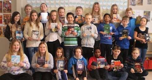 Gruppbild av eleverna i årskurs 5 vid Östervåkla skola vårterminen 2015 där alla visar upp en bok