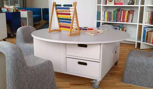 Vitt barnbord med små grå barnstolar.