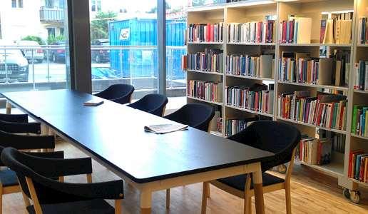 Interiör från Knivsta bibliotek med ett långt bord med svarta stolar.