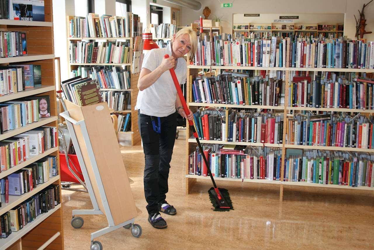 Kvinna moppar golv bland bokhyllor