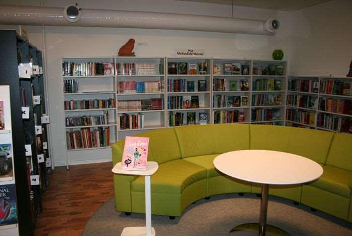 Grön soffa med bokhyllor bakom